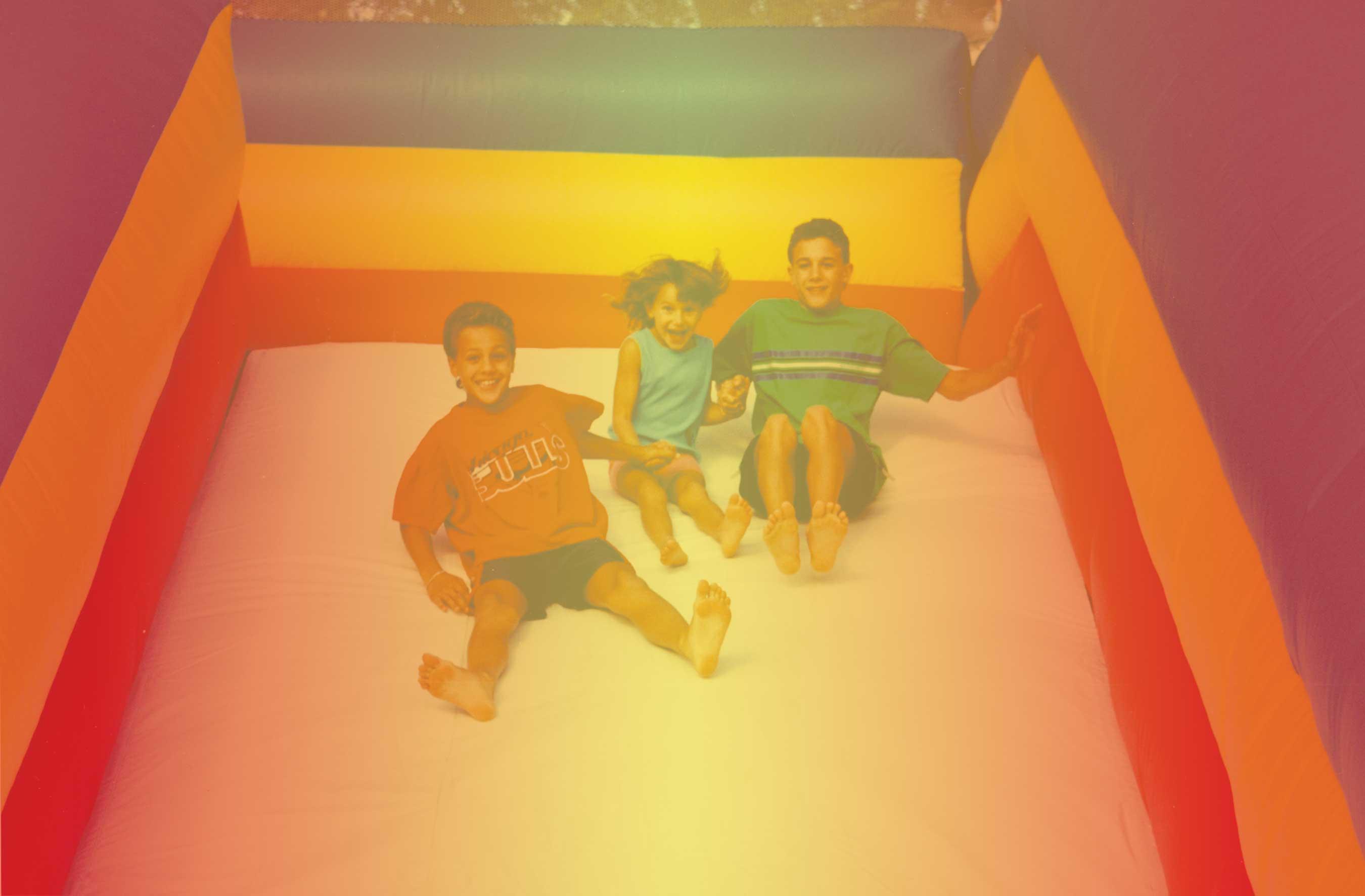 3 kids holding hands inflatable slide